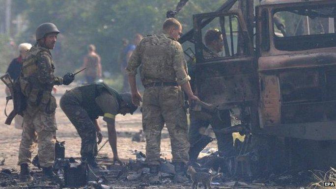 Xe của quân đội Ukraine cháy đen do trúng pháo kích của phe ly khai. Ảnh: EPA