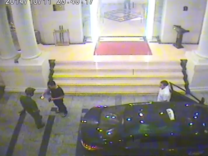 Hình ảnh camera của khách sạn ghi lại cảnh người đàn ông áo đen đưa 1 thứ cho người mặc sắc phục công an xem. Sau đó người mặc sắc phục bỏ đi
