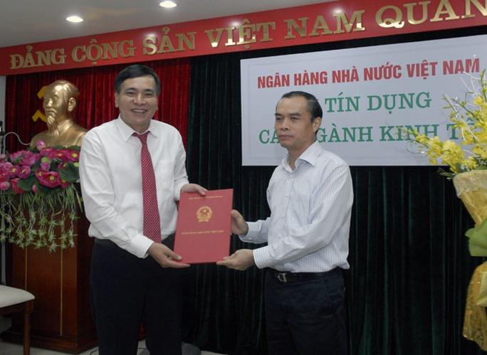 Ông Nguyễn Tiến Đông (trái) nhận quyết định điều động lên làm Vụ trưởng Vụ tín dụng Ngân hàng Nhà nước.
