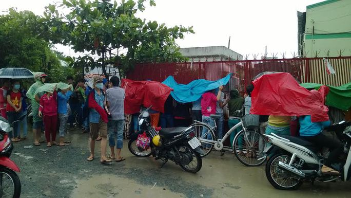 Dù trời mưa to các công nhân vẫn kiên trì bám trụ công ty để đòi lương