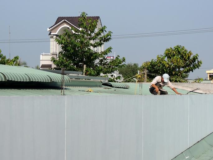 Công nhân leo lên nóc nhà kho để tháo dỡ mái tôn. Ảnh: D.M.Phương