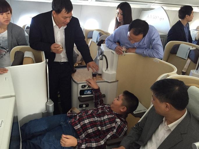 Một hành khách nhí thích thú trải nghiệm giường nằm bằng cách bấm nút điều khiển để hạ ghế nằm phẳng - 80 độ. Đây là ghế đặc biệt của hạng thương gia