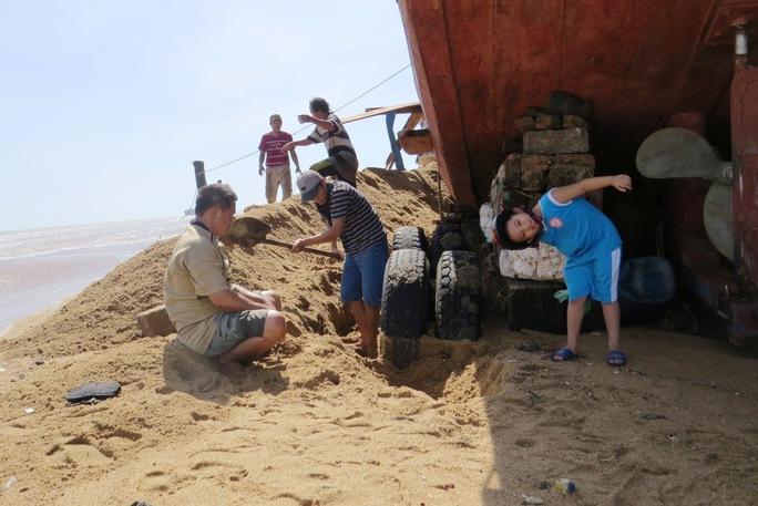Người dân đang moi cát để đưa tàu thuyền ra khỏi khu vực bị triều cường vùi lấp