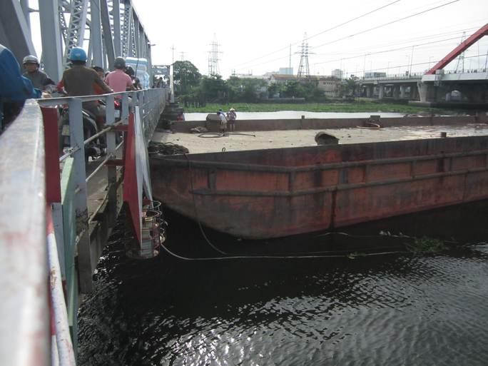 Mực nước quá cao khiến chiếc sà lan bị kẹt lại rồi đội ngược gầm cầu Bình Lợi