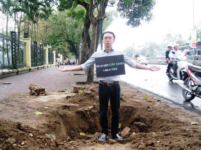 Anh Nguyễn Anh Tuấn với tấm bảng giữa trời mưa kêu gọi người dân chung tay bảo vệ cây xanh trong thành phố