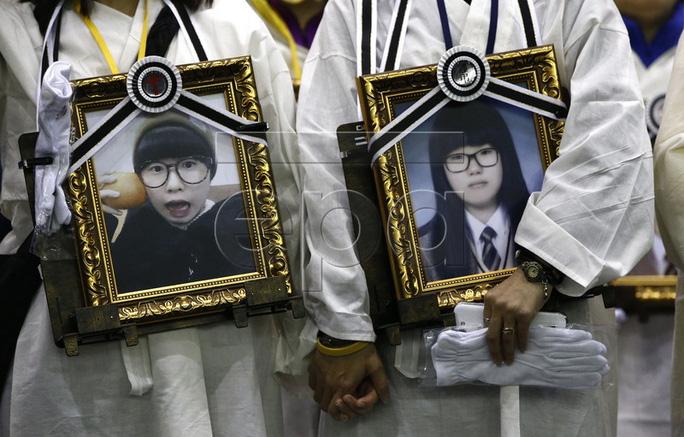 Các bậc phụ huynh ôm di ảnh con cái họ trước khi diễu hành đến Seoul hôm 4-4. Ảnh: EPA