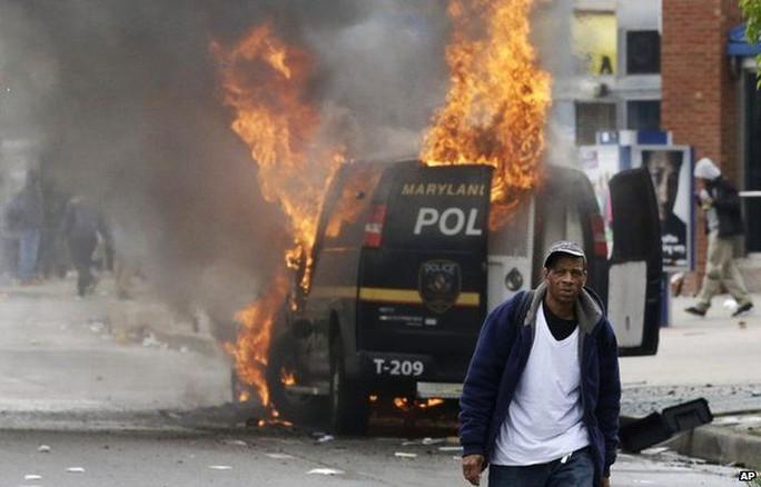 Người biểu tình đốt xe cảnh sát ở bang Maryland. Ảnh: AP