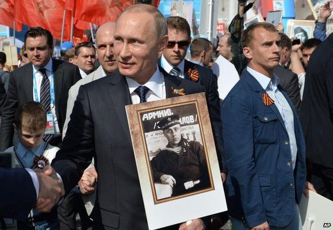 Tổng thống Putin cầm di ảnh của người cha quá cố tuần hành tại lễ duyệt binh hôm 9-5. Ảnh: AP