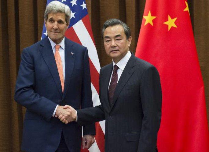 Ngoại trưởng Mỹ John Kerry bắt tay người đồng cấp Trung Quốc Vương Nghị trước cuộc họp tại Bộ Ngoại giao ở Bắc Kinh hôm 16-5. Ảnh: Reuters