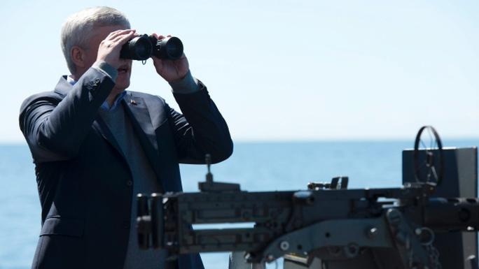 Thủ tướng Canada Stephen Harper dùng ống nhòm theo dõi 2 tàu khu trục Nga. Ảnh: Canadian Press