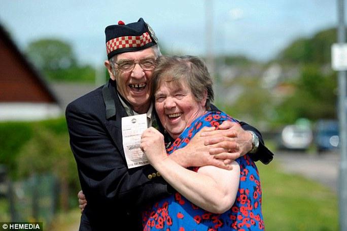 Vợ chồng ông Geordie Rhodick hạnh phúc với tờ vé số trúng giải. Ảnh: HEMEDIA