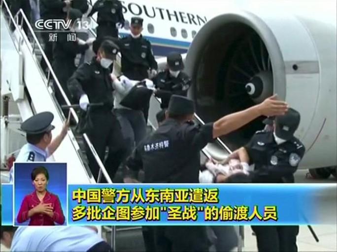 109 người Duy Ngô Nhĩ xuống máy bay tại Trung Quốc hồi tháng 7. Ảnh: CCTV