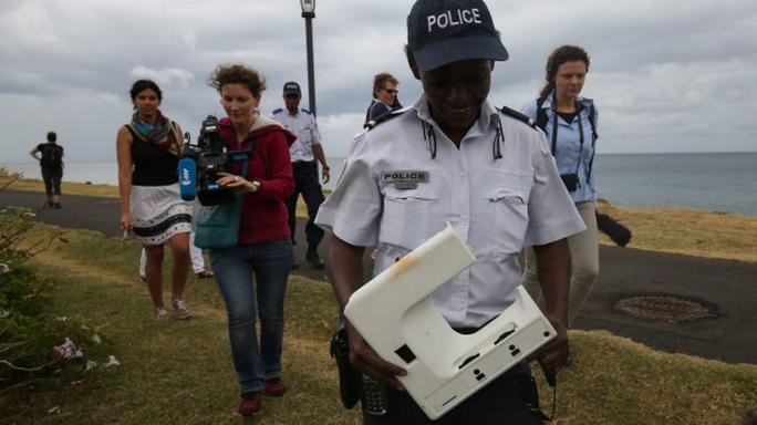 Sĩ quan Gisele Cadar cầm mảnh nhựa đem về văn phòng Cảnh sát Quốc gia. Ảnh: SMH