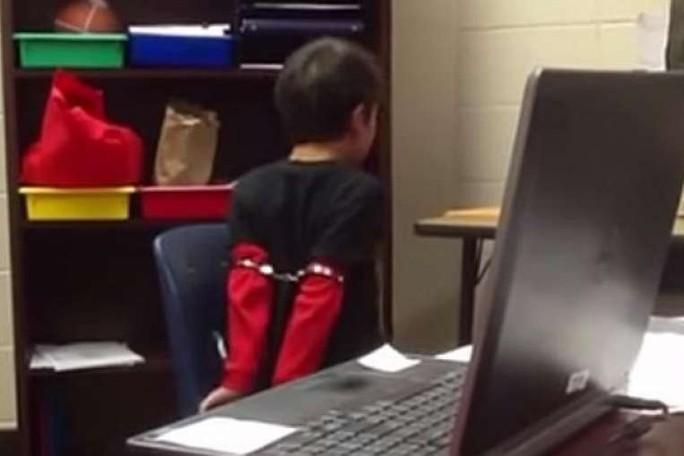 Cậu bé bị còng tay trong đoạn video. Ảnh: Youtube