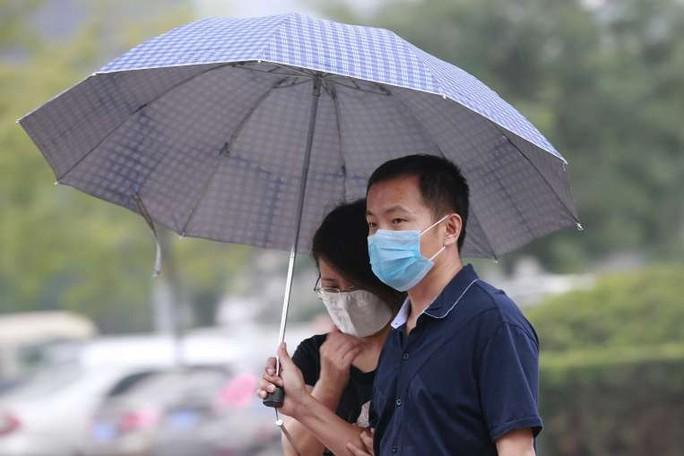 Một cặp đôi che dù đi dưới mưa ở TP Thiên  Tân ngày 18-8. Ảnh: Reuters