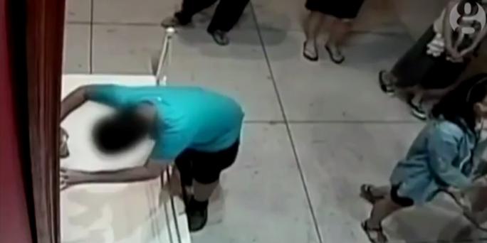 Cậu bé ngã và chống tay vào bức tranh. Ảnh: The Guardian