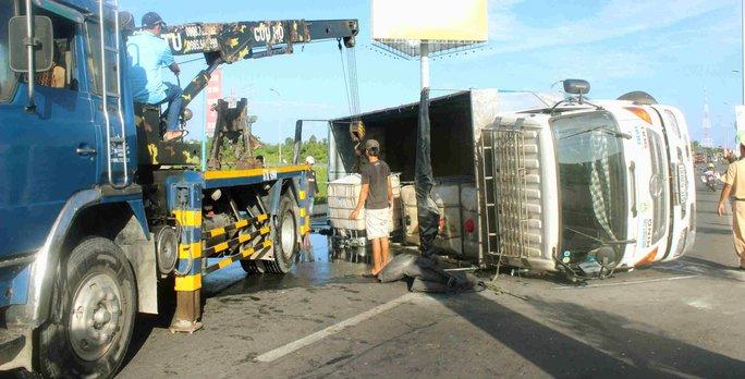Xe cứu hộ đang cẩu chiếc xe tải bị lật ngang giữa đường