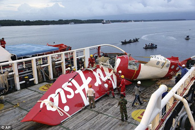 Crew members of the Crest Onyx ship untie parts of the tail section of AirAsia Flight OZ8501 at Kumai port in Pangkalan Bun, Indonesia