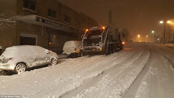 A garbage truck driver attempts to fulfill his early morning duties after roads were blanketed in white powder