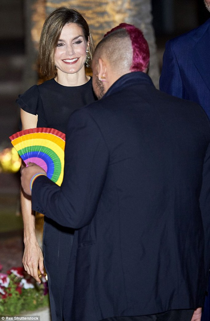 All smiles: Letizia beams as she chats to a man with a quirky purple mohican and a rainbow fan