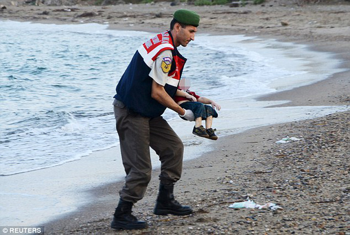 A policeman on a Turkish beach gently recovers the body of Aylan who drowned as his family tried to make their way to the Greek island of Kos yesterday