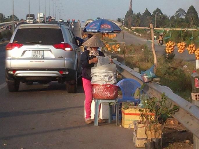 Xe ô tô dừng lại mua thanh trà ngay dưới dốc cầu Cần Thơ