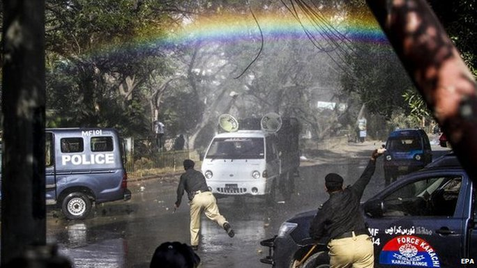 A rainbow appears over the street as Pakistani police use water cannon vehicles to disperse protesters in Karachi, Pakistan, 16 January