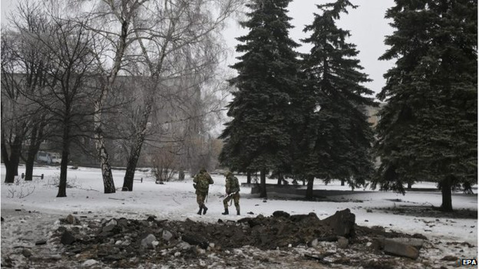 Ukrainian servicemen pass the crater of a shell in the city centre of Debaltseve, 22 January 2015