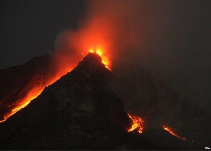 Mount Sinabung spews hot gas and lava as seen from Tiga Serangkai village in Karo, North Sumatra, Indonesia, 14 June 2015