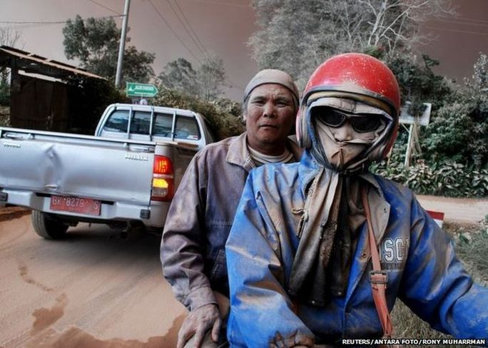 Residents with faces covered in ash ride on a motorcycle as Mount Sinabung volcano erupts, in Sukandebi village in Karo Regency, Indonesias North Sumatra province, June 13, 2015