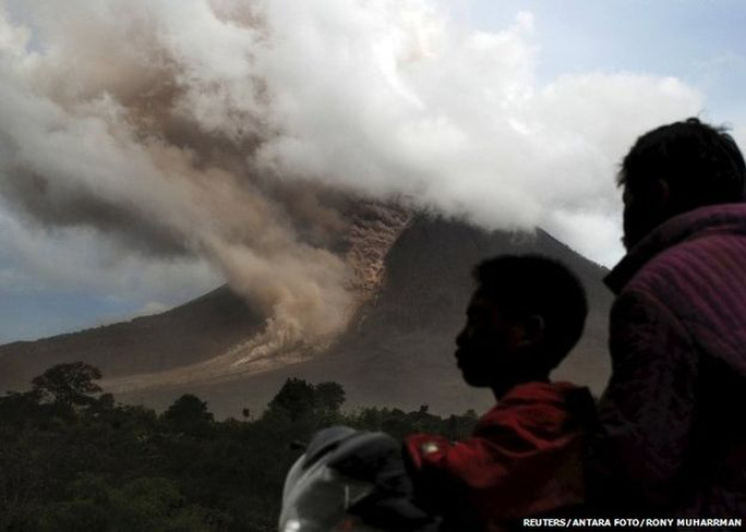 Residents sit on their motorcycle as they watch an eruption at Mount Sinabung, in Namanteran village in Karo Regency, Indonesias North Sumatra province, June 14, 2015
