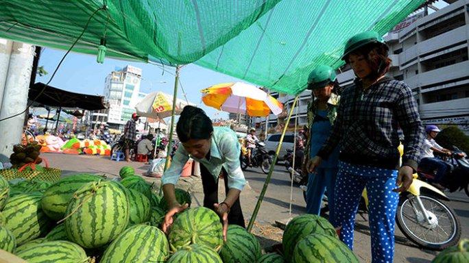 Quầy hàng dưa hấu của chị Nguyễn Thị Nhị trên đường Phan Đăng Lưu quảng cáo giá bán 12.000 đồng/kg nhưng khách trả 10.000 đồng/kg chị cũng bán -  Ảnh: Thanh Tùng