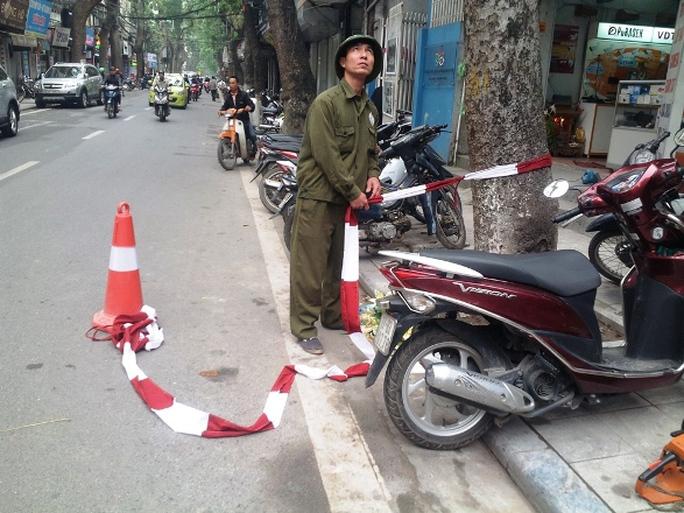 Công nhân dùng dây phong toả quanh khu vực chặt cây, đảm bảo an toàn cho người dân