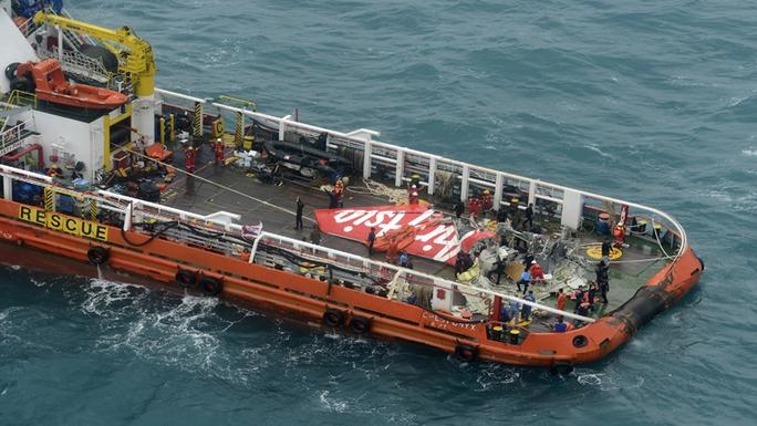 Phần đuôi máy bay được đưa lên tàu. Ảnh: CNA