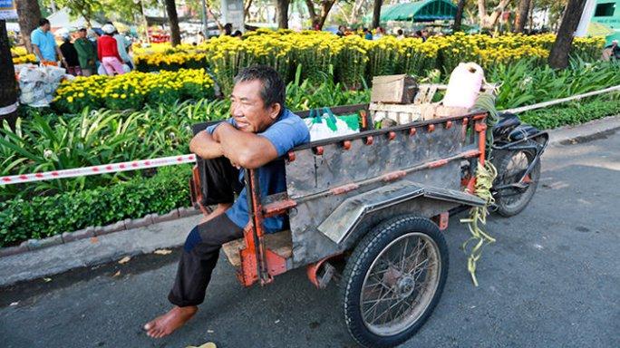 Hoa quả tết không bán được kéo theo nghề chở hoa quả thuê cũng ế ẩm. Trong ảnh: ông Nguyễn Văn Châu (ở Q.4, TP.HCM) chờ khách thuê chở hoa quả tết trên đường Trần Hưng Đạo - Ảnh: Tiến Thành