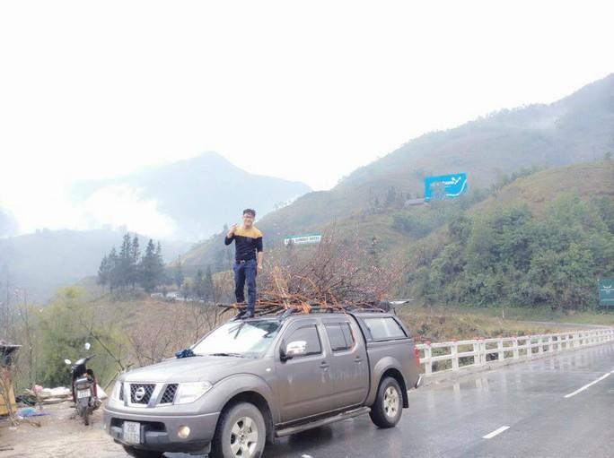 Một thanh niên hân hoan sau khi mua được cành đào rừng ưng ý