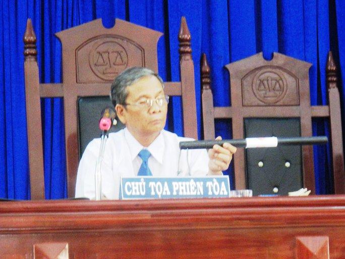 Chủ tọa Nguyễn Phi Đô đưa vật chứng gậy cao su để bị cáo Thành xác định