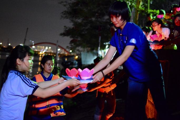 Các bạn sinh viên chuyền tay nhau những chiếc hoa đăng để thả trên sông. Ảnh: Thăng Bình.