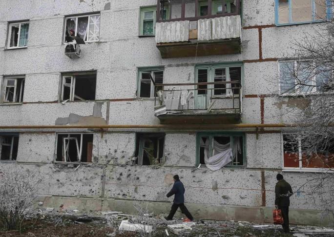 Cư dân Svitlodarsk ở miền Đông Ukraine bên ngoài những tòa nhà tan hoang. Ảnh: Reuters