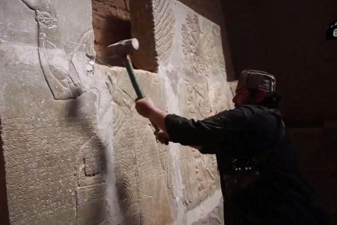 Đoạn video chiếu cảnh một tay súng IS phá hủy di tích tại thành cổ Nimrud Ảnh: Abc.net.au