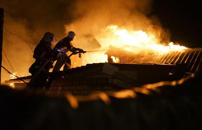 Nhân viên cứu hỏa chữa cháy tại một ngôi nhà bị pháo kích ở Donetsk, miền Đông Ukraine Ảnh: AP