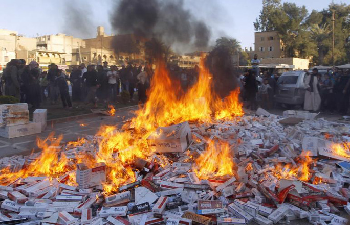 IS tiêu hủy hàng ngàn bao thuốc lá thu được ở TP Raqqa - Syria. Ảnh: Reuters