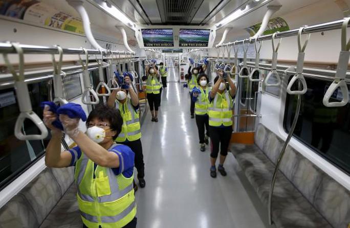 Công nhân Hàn Quốc khử trùng và vệ sinh tàu điện ngầm. Ảnh: Reuters