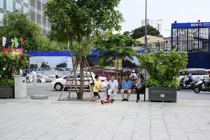 Ba cụ già ngồi vui chơi với con cháu bên hành lang quảng trường đi bộ. Ảnh: Thăng Bình