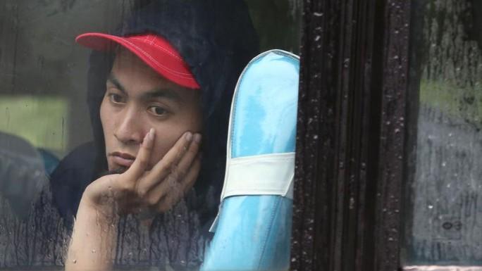 Một người dân Philippines trú mưa trong khi đường sá tắc nghẽn. Ảnh: AP