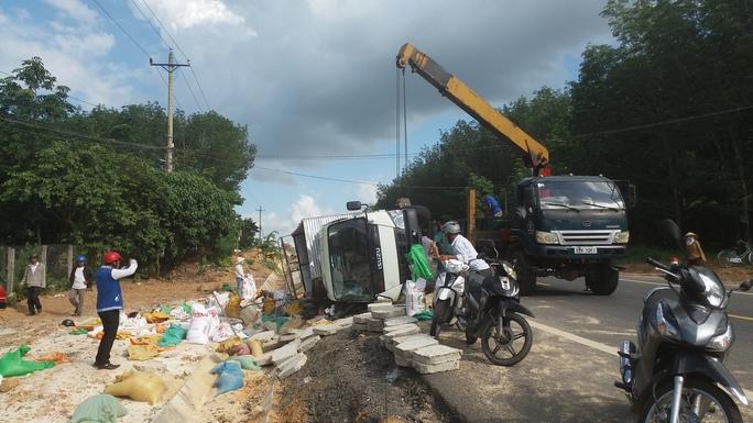 Chiếc xe tải lật nghiêng khiến hàng chục bao gạo đổ ra vệ đường