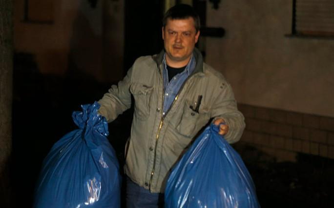 Một điều tra viên xách những túi chứa vật dụng lấy từ nhà cơ phó Lubitz. Ảnh: AP