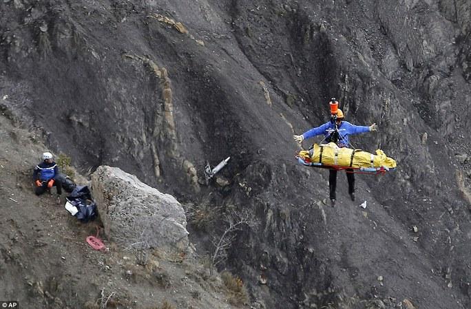 Nhân viên cứu hộ được kéo lên trực thăng với một túi đựng thi thể. Ảnh: AP