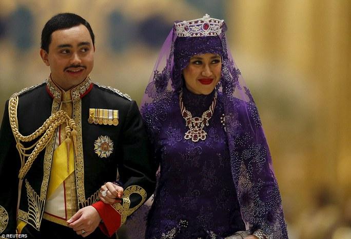 Chú rể mặc quân phục, cổ áo nạm kim cương trong khi cô dâu mặc bộ váy dài màu tím. Ảnh: Reuters