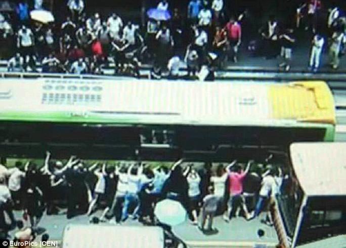 Tóc và quần áo bà cụ bị mắc kẹt bên dưới bánh xe buýt nên mọi người chỉ còn cách nâng xe buýt. Ảnh: CEN